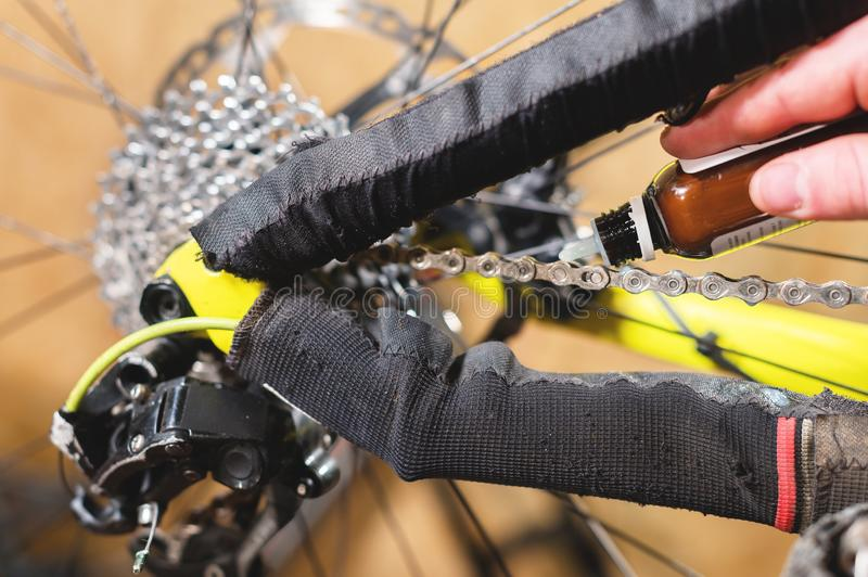 Close-up of a man`s hand, led by masters, lubricate the bicycle chain of a mountain bike with a special lubricant in the. Home workshop stock images