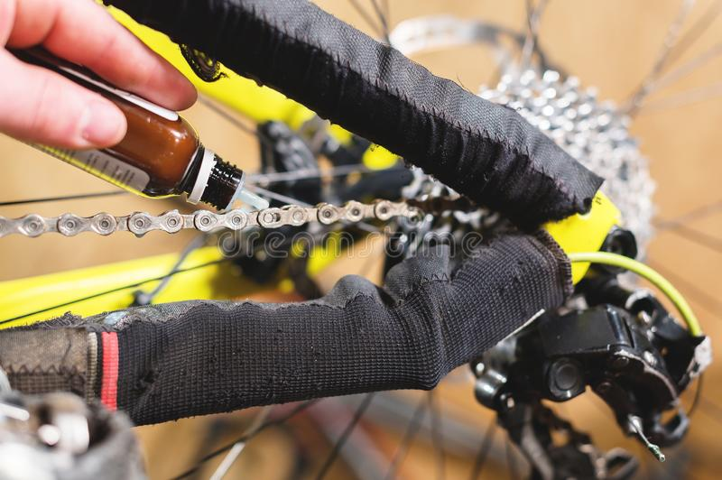 Close-up of a man`s hand, led by masters, lubricate the bicycle chain of a mountain bike with a special lubricant in the. Home workshop stock photo