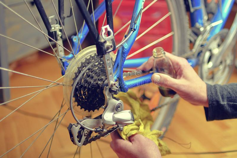 Close-up of a man`s hand, lubricate the bicycle chain of a bike with a special oil in the home workshop.  royalty free stock image