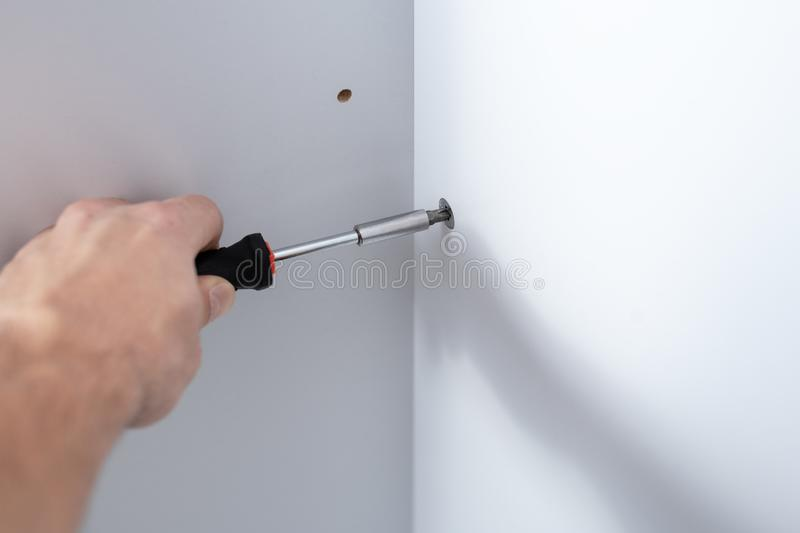 Large male hand with a manual screwdriver point in the Assembly of furniture. Close-up of a man`s hand with a manual screwdriver twists the bolt into a piece of royalty free stock photos