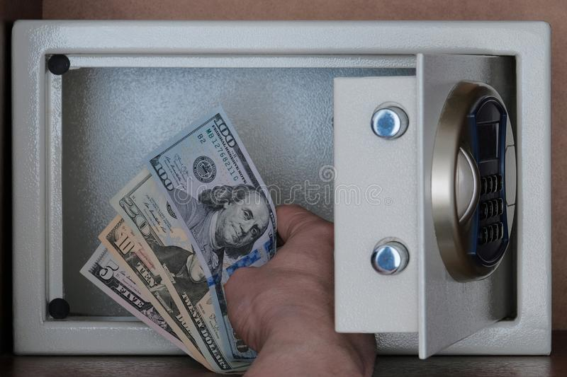 Close-up of a man`s hand putting American dollars in a safe Deposit box. Banknotes of 5, 10, 20, 100 US dollar. Storage of money, royalty free stock images