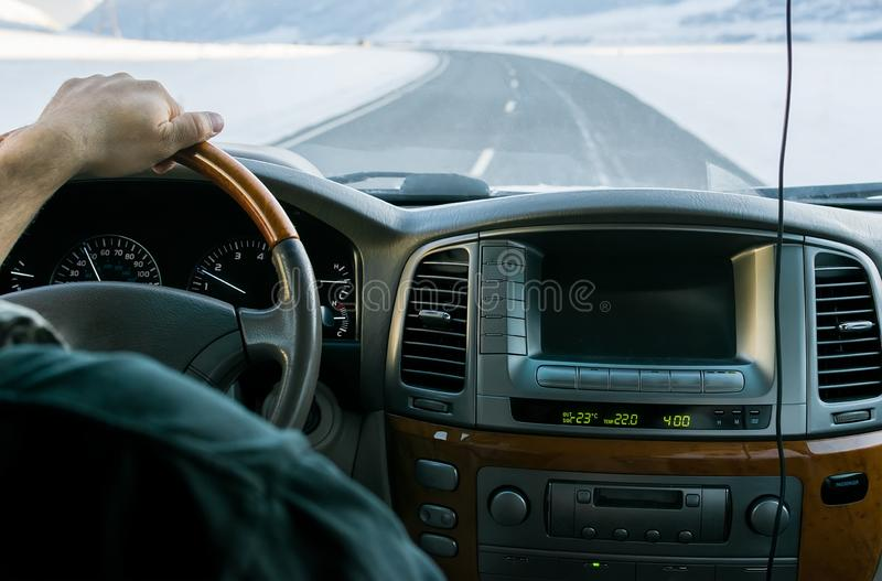 Close-up of a man hand on the steering wheel of a car that moves on a snowy road. Among the mountains in the winter stock image