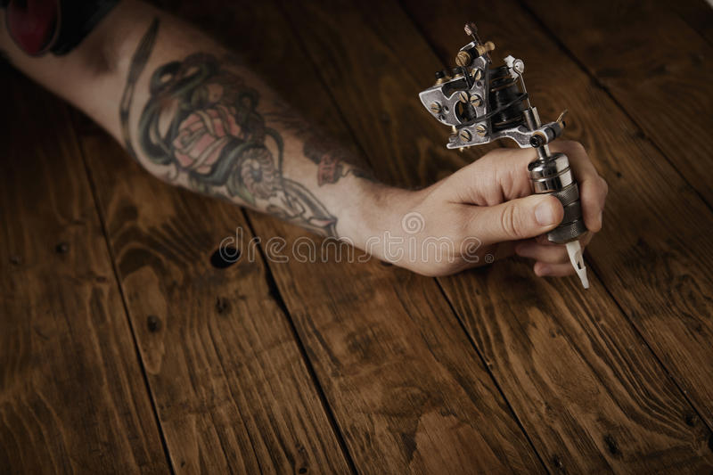 Close up of a man`s hand with tattoo gun. Close up of a man`s hand holds new custom made steampunk style tattoo gun above brushed vintage wooden table stock photo