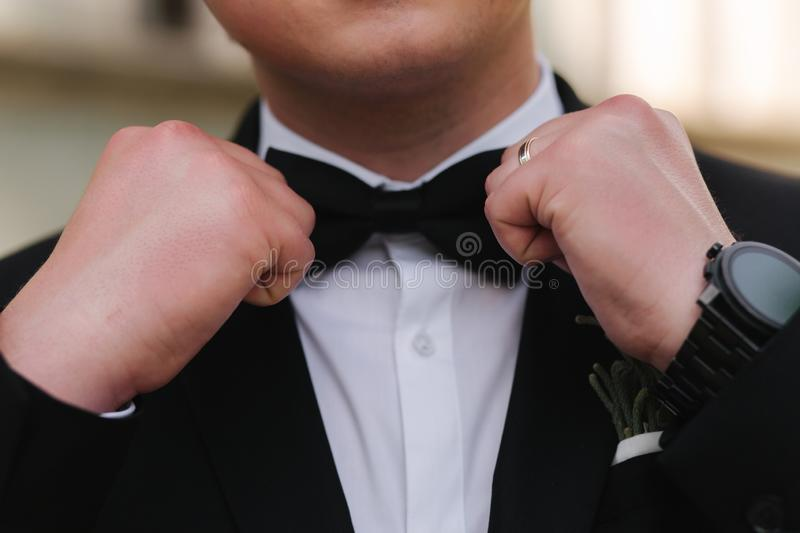 Close up of man`s hand on tie bow stock images