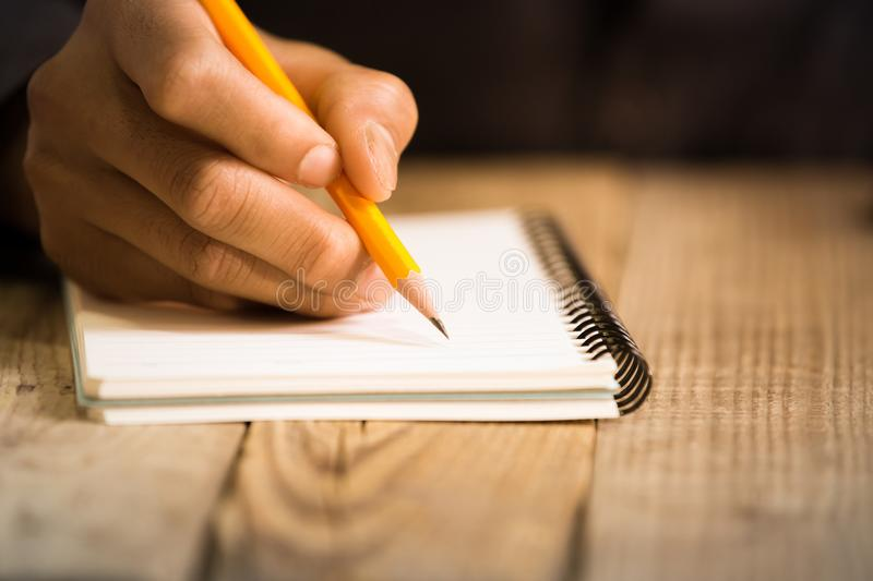 Close Up on a man`s hand writing on paper with a pencil royalty free stock image