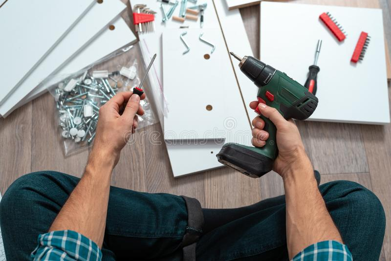 Man`s hands with tools to assemble furniture sitting on the floor. Close up man`s hands with tools to assemble furniture sitting on the floor. the concept of stock photography