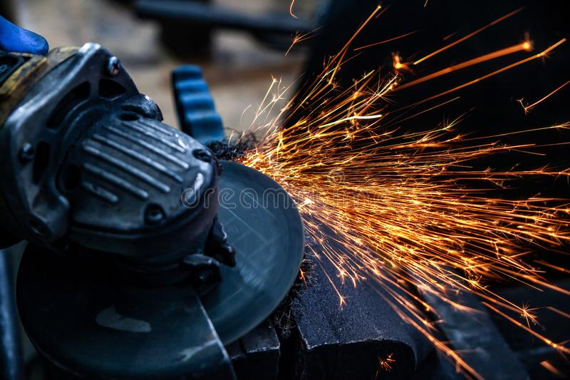 Metal melting. Close-up of a man sawing   bearing metal brake disk with a hand circular saw, bright flashes flying in different directions, in the background royalty free stock photos