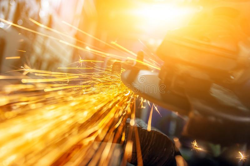 Close-up of a man sawing. Bearing metal with a hand circular saw, bright flashes flying in different directions, in the background tools for an auto repair shop stock photo