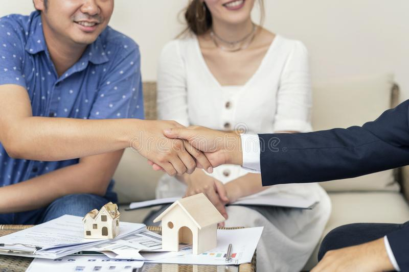 Close up, Man shaking hands represent sale, Asian couple meeting financial adviser for home, real estate purchase, success stock image