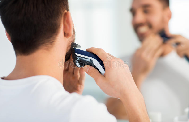 Close up of man shaving beard with trimmer. Beauty, shaving, grooming and people concept - close up of young man looking to mirror and shaving beard with trimmer royalty free stock image