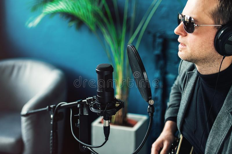 Close up of a man singer sitting on a stool in a headphones with a guitar recording a track in a home studio stock photography