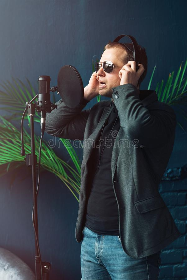 Close up of a man singer in a headphones recording a song in a home studio. Man wearing sunglasses, jeans, black shirt and a jacket. side view stock images
