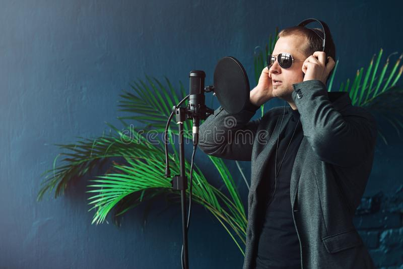 Close up of a man singer in a headphones recording a song in a home studio. Man wearing sunglasses, black shirt and a jacket. side view stock photo