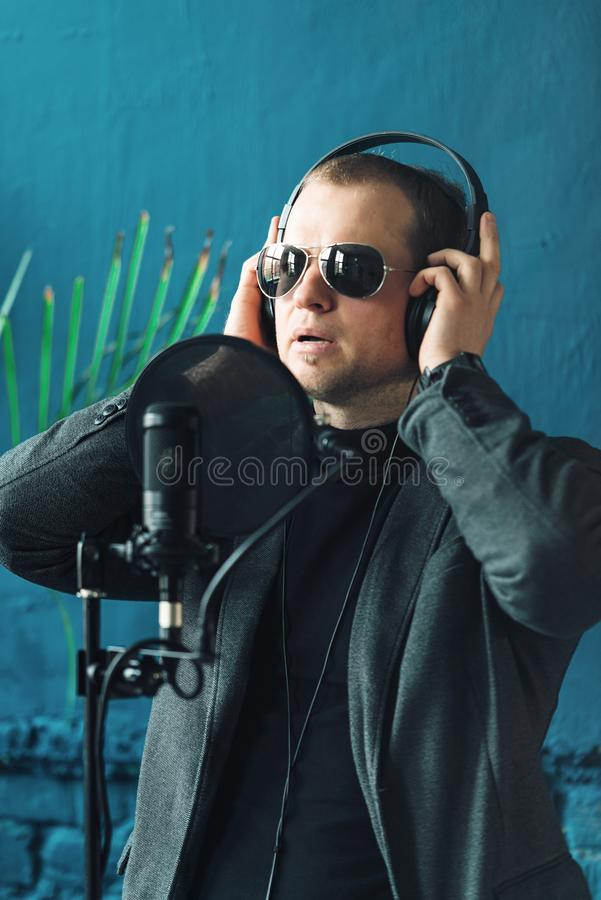 Close up of a man singer in a headphones recording a song in a home studio. Man wearing sunglasses, black shirt and a jacket. side view stock photography