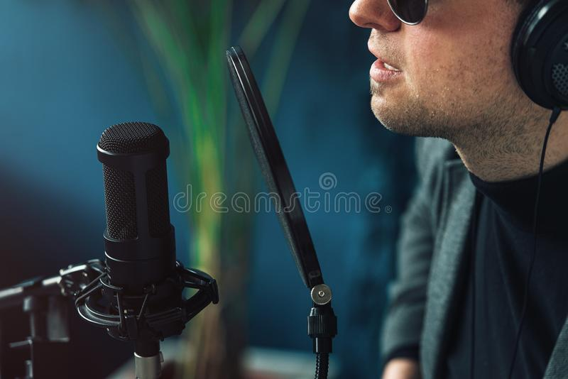 Close up of a man singer in a headphones recording a song in a home studio. Man wearing sunglasses, black shirt and a jacket. side view royalty free stock photography