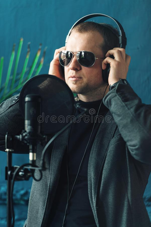 Close up of a man singer in a headphones recording a song in a home studio stock photo