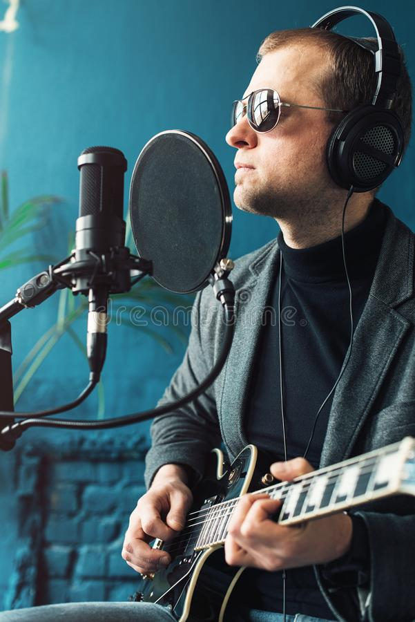 Close up of a man singer sitting on a stool in a headphones with a guitar recording a track in a home studio royalty free stock images