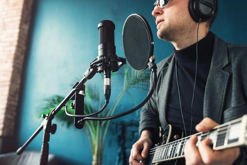 Close up of a man singer sitting on a stool in a headphones with a guitar recording a track in a home studio stock image