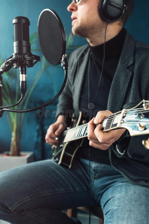 Close up of a man singer sitting on a stool in a headphones with a guitar recording a track in a home studio royalty free stock image