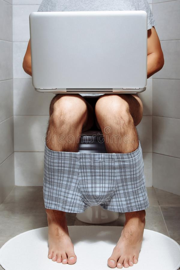 Close-up of a man sitting on the toilet using laptop royalty free stock photos