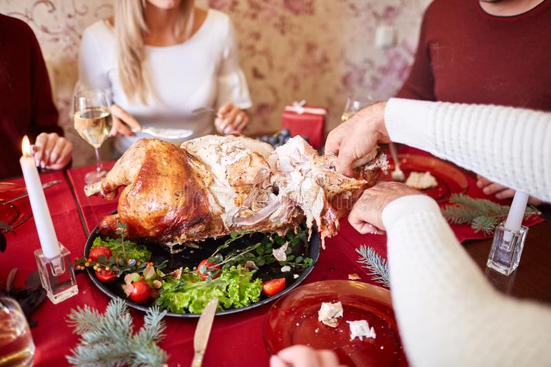 Man cutting roasted turkey on a table background. Family enjoying autumn holidays. Thanksgiving dinner concept. royalty free stock photo