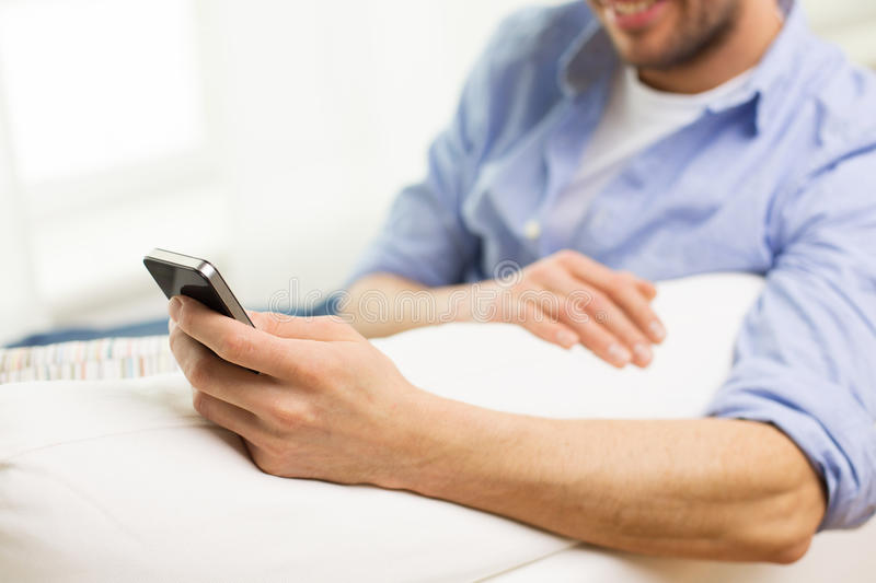 Close up of man with smartphone at home royalty free stock image