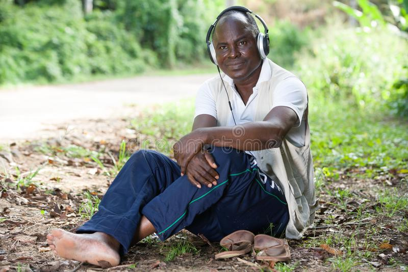 Close-up of a man smiling and expressing happiness sitting in a park and listening to music stock photo