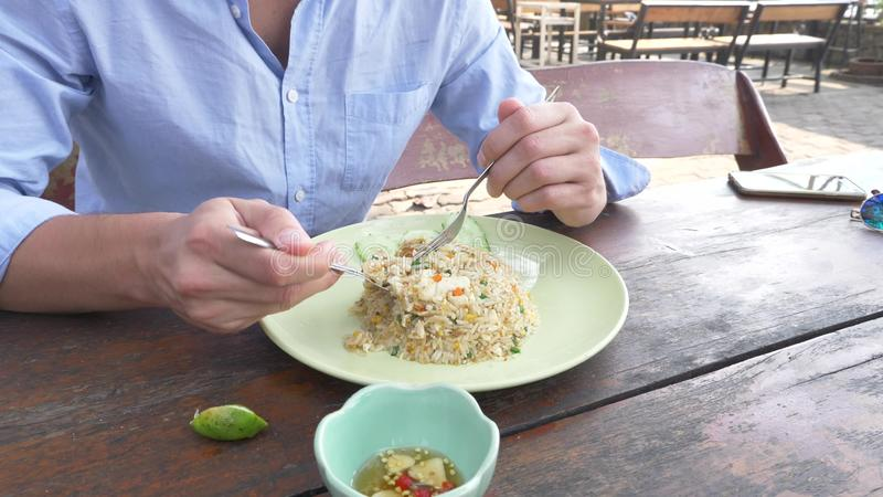 Close-up. man squeezes lime juice on a dish with stir fried Jasmine rice with egg and shrimps, decorated with cucumber. Close-up. man squeezes lime juice on a stock photography