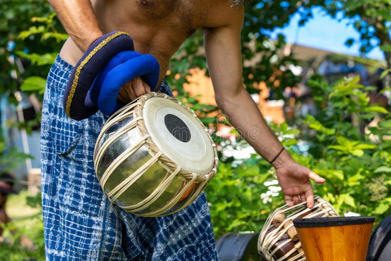 Spiritual man holding music instruments. A close up on man standing and holding drums, traditional music instruments during a live music performance While royalty free stock images