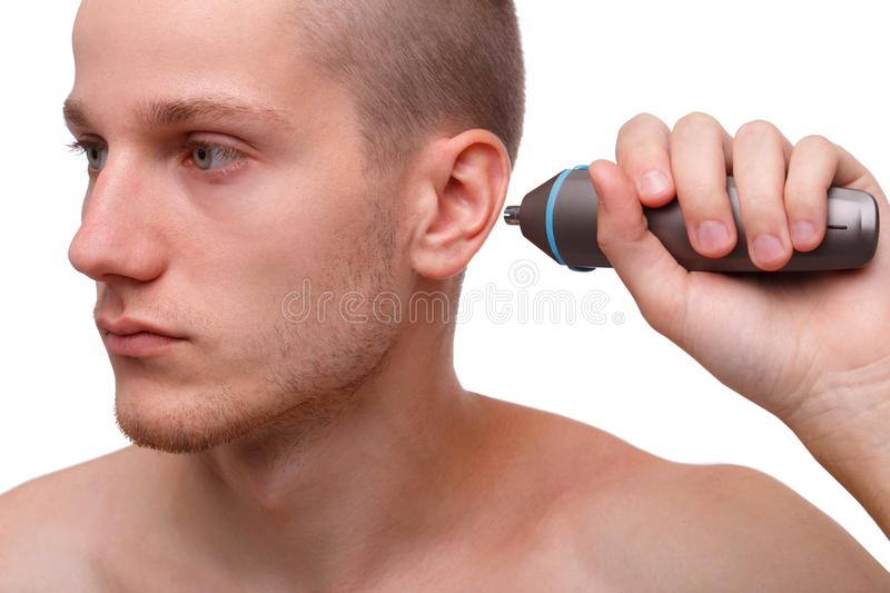 Close-up of a man with a trimmer near his ear isolated on white background. Removal of excess hair. The concept of hygiene, self-care royalty free stock photography