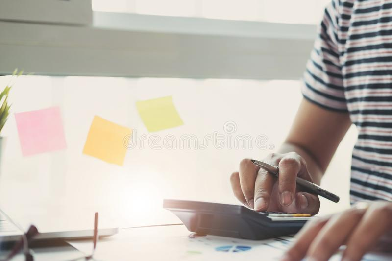 Close up man using calculator and laptop for do math finance on wooden desk in office and business working background, tax, royalty free stock photo