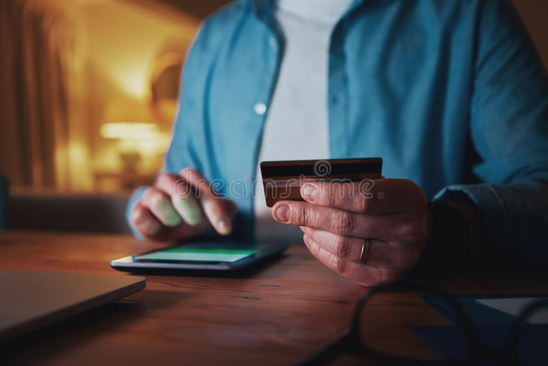 Close-up of man using credit card for paying on smart phone. Close-up man`s hands holding a credit card and using cell phone for online shopping at night royalty free stock photography