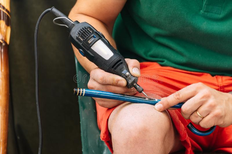 Close up of a man using a machine to make the details on a wooden stick royalty free stock photos