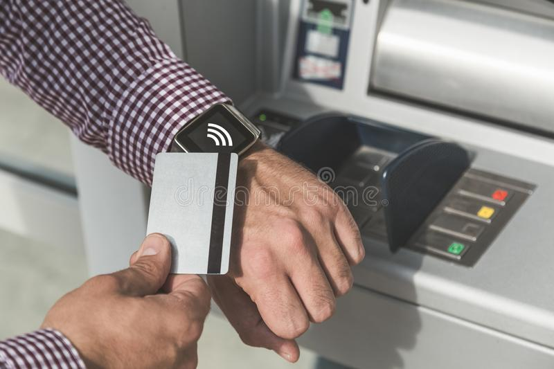 Man making payment by using smartwatch and debit card outdoors. Close up of man using wireless payment system with credit card and smart watch next to atm royalty free stock photo
