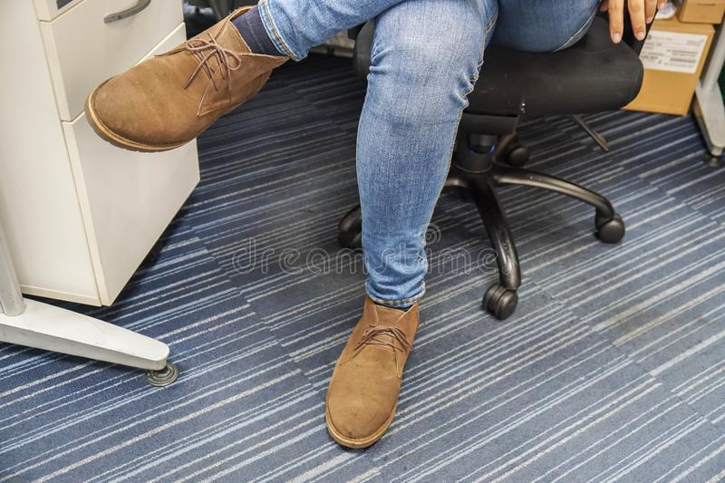 Close up man wear blue jeans and brown leather shoes sit and cross his legs on office chair royalty free stock photo