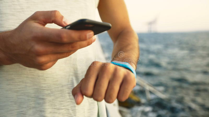 Close up of man wearing white t-shirt checking miles on his fitness tracker royalty free stock images