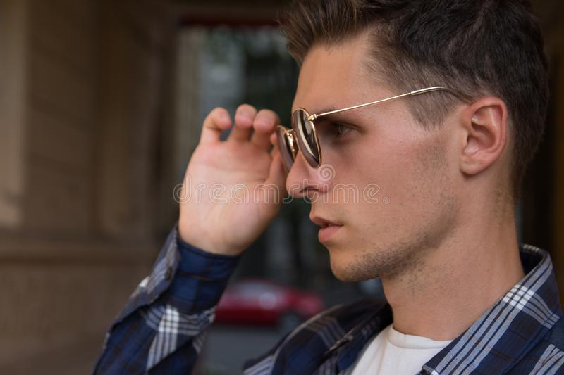 Close-up of a man who takes off his sunglasses,male portrait in profile, where he holds glasses, touches glasses.buying points. Close-up of a man who takes off royalty free stock image