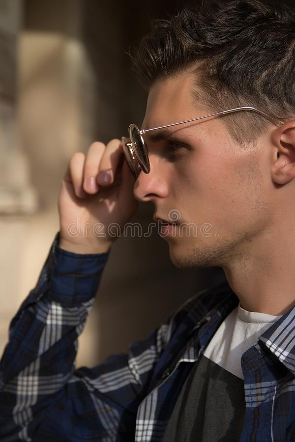 Close-up of a man who takes off his sunglasses,male portrait in profile, where he holds glasses, touches glasses.buying points. Close-up of a man who takes off stock photos