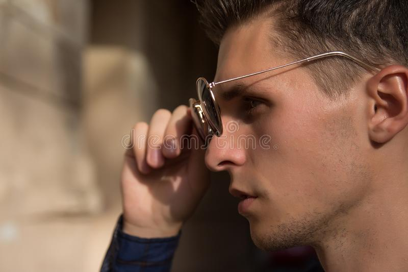 Close-up of a man who takes off his sunglasses,male portrait in profile, where he holds glasses, touches glasses.buying points. Close-up of a man who takes off stock photography