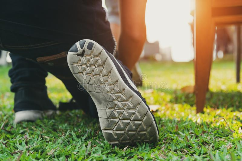 Close up of man who wearing running shoes in park before ready to start and go. Business and Sport concept. People and Nature. Theme. Green grass element. Back stock photos