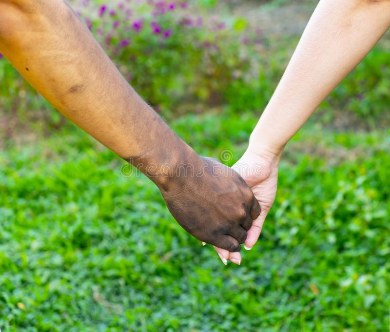 Close up man and woman hands touching holding together on blurred background for love valentine day concept, shake hand with a d. Irty hand and a clean, Stained stock photography