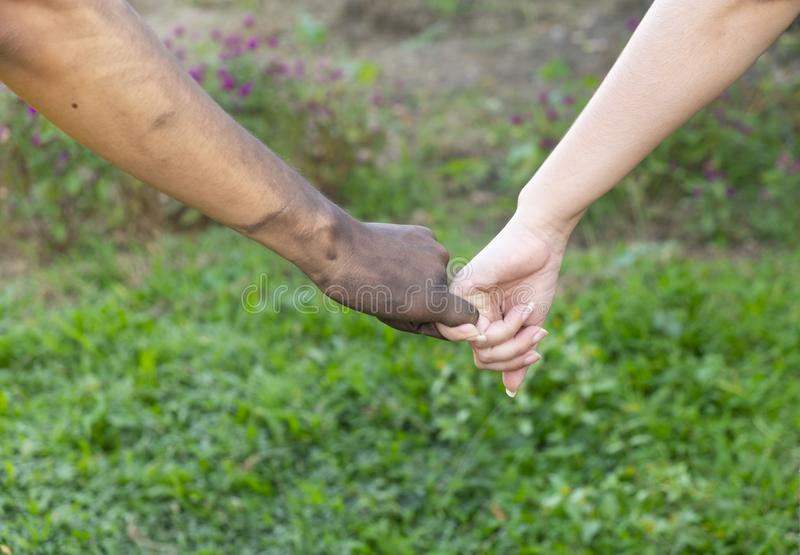 Close up man and woman hands touching holding together on blurred background for love valentine day concept, shake hand with a d. Irty hand and a clean, Stained royalty free stock photo