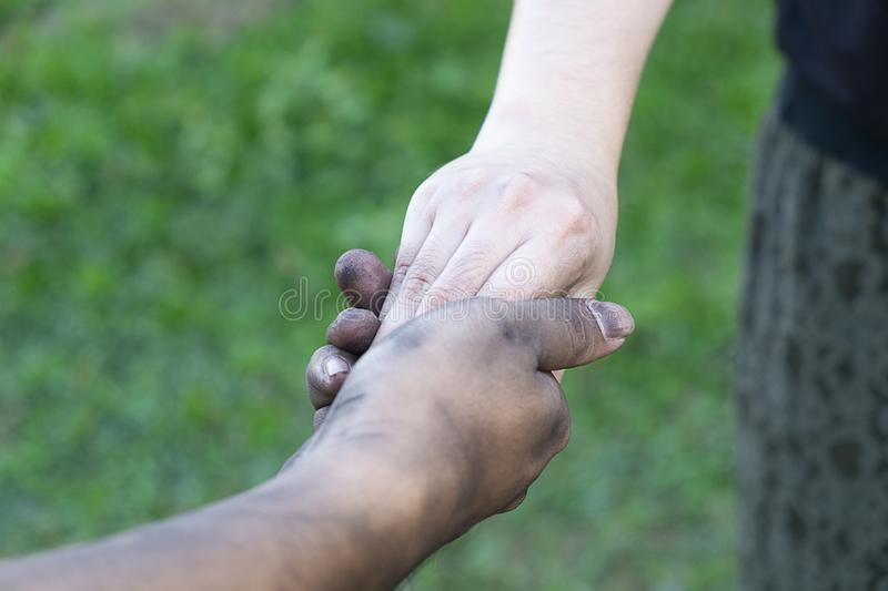 Close up man and woman hands touching holding together on blurred background for love valentine day concept, shake hand with a d. Irty hand and a clean, Stained stock image