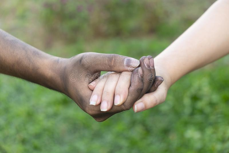 Close up man and woman hands touching holding together on blurred background for love valentine day concept, shake hand with a d. Irty hand and a clean, Stained royalty free stock photography