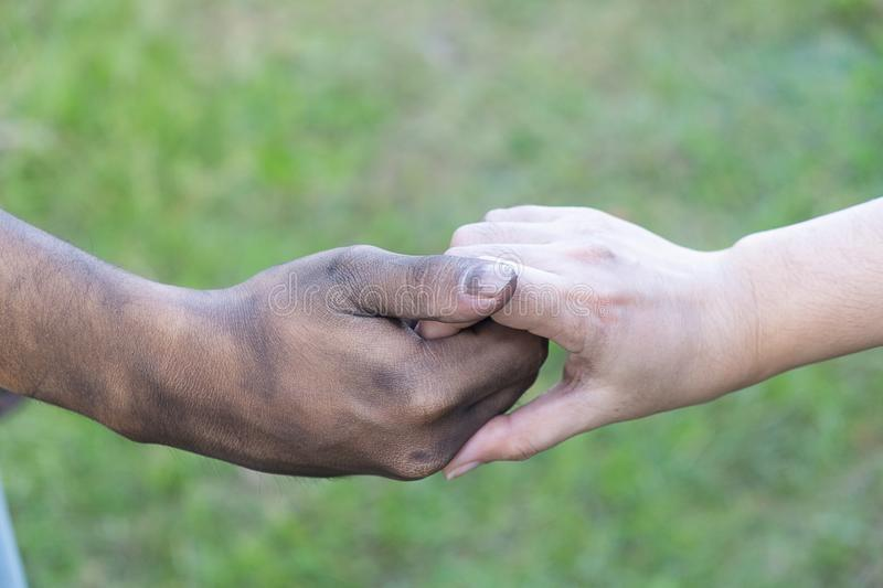Close up man and woman hands touching holding together on blurred background for love valentine day concept, shake hand with a d. Irty hand and a clean, Stained royalty free stock photos