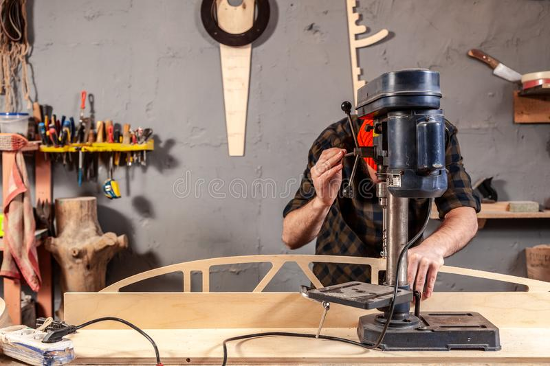 Home repair concepts. Close up of a man with work clothes and a carpenter`s cap is carving a wooden board on an modern large drilling machine in a light workshop royalty free stock photography