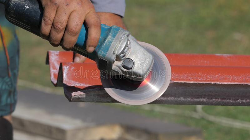 Close-up of man in working clothes cutting a list of red steel roofing by metal cutting saw. Clip. Materials and. Close-up of man in working clothes cutting a stock photo