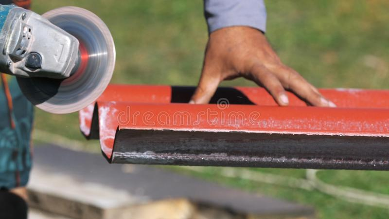 Close-up of man in working clothes cutting a list of red steel roofing by metal cutting saw. Clip. Materials and. Close-up of man in working clothes cutting a royalty free stock images