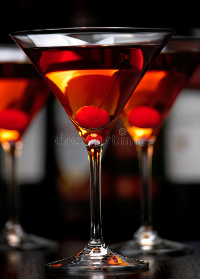 Close-up manhattan drinks with cherry with bar in the background stock photo