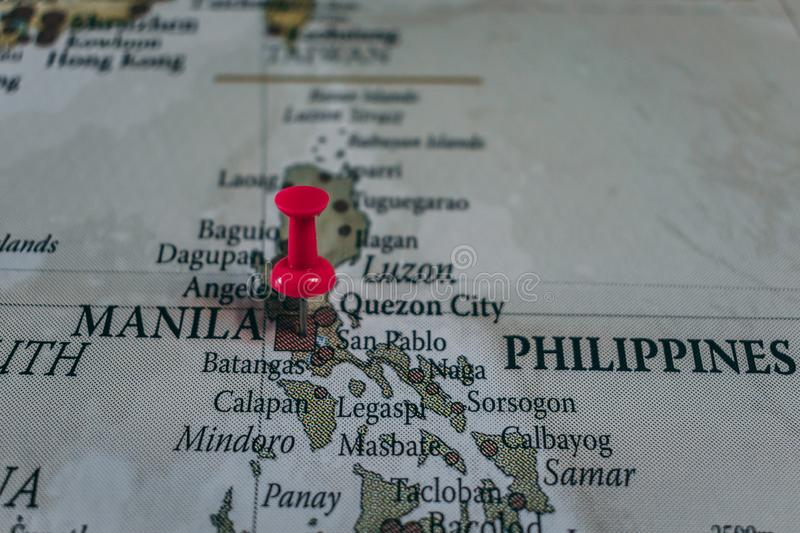 Close up of Manila pin pointed on the world map with a pink pushpin. Capital city of Philippines stock images